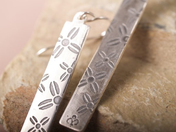 Rectangle dangle sterling silver earrings on French hooks with an etched pattern of large and small cross-shaped flowers shot close up on sandstone