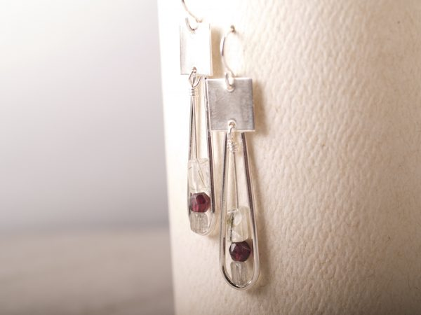 sterling silver earrings with square at the top and long sweeping loop that dangles. Pendulum of garnet and labradorite hangs inside the loop. Shown hanging on a white background