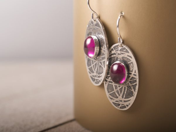 sterling silver oval earrings with an orbiting curve pattern and ruby cabochons on French hooks on gold background