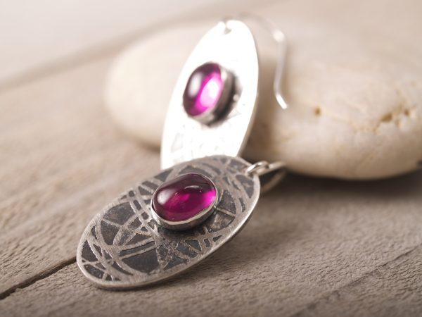 sterling silver oval earrings with an orbiting curve pattern and ruby cabochons on French hooks leaning on a stone on barn wood