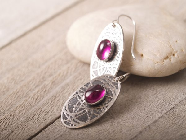 sterling silver oval earrings with an orbiting curve pattern and ruby cabochons on French hooks on stone