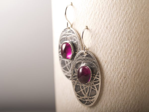 sterling silver oval earrings with an orbiting curve pattern and ruby cabochons hanging on French hooks on a white background