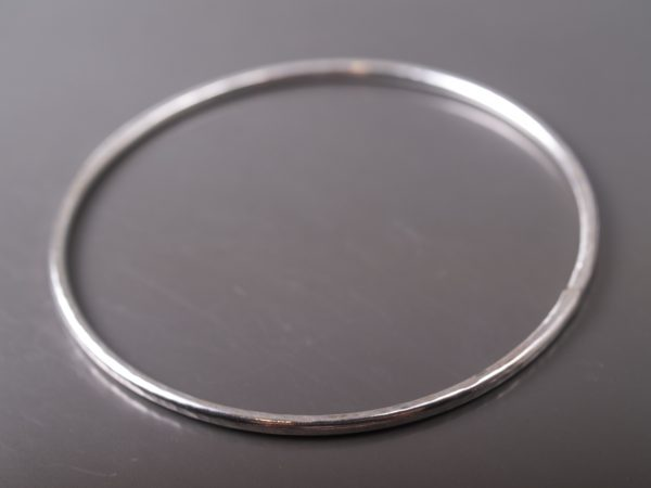 Sterling silver circle bangle with hammered finish shot on a satin smoke grey background