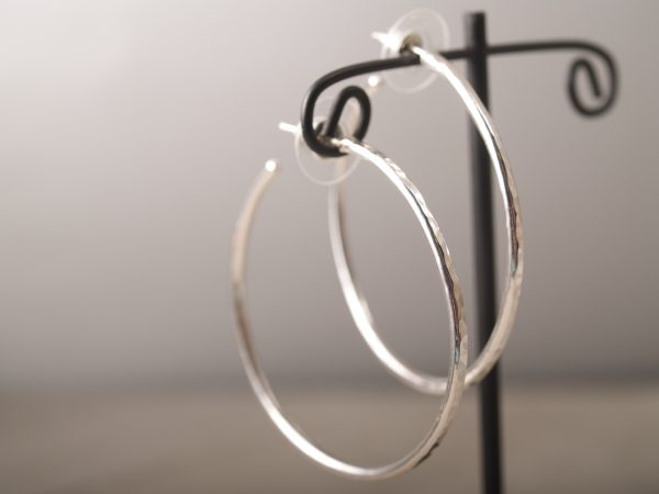 hammered sterling silver hoop earrings with disk backs hanging on an earring stand