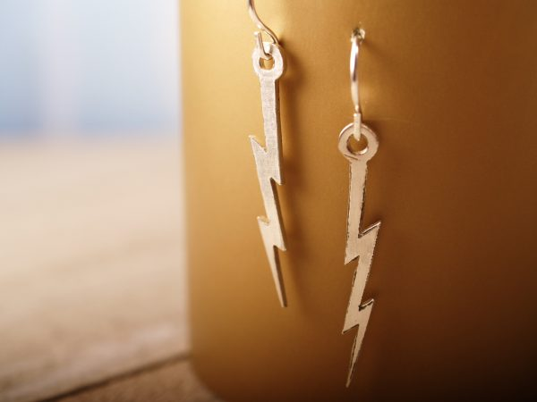 lightning bolt French hook earrings hanging on a gold background
