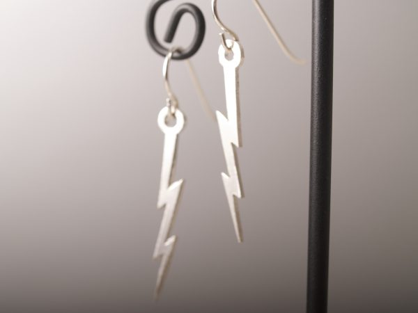 lightning bolt French hook earrings hanging on grey background