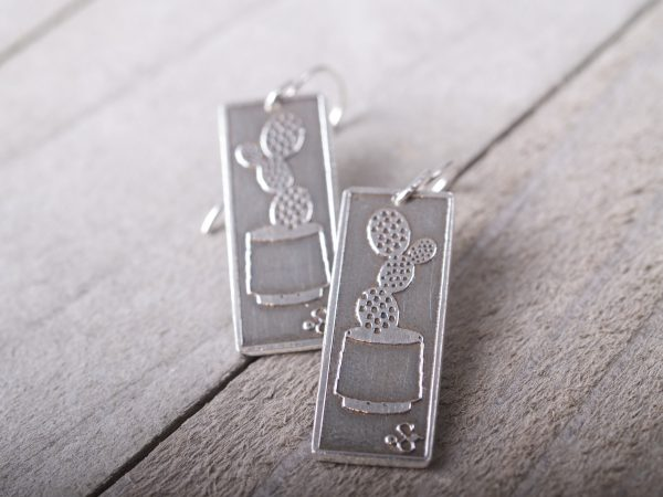 long rectangle etched sterling earrings with prickly pear cactus in a pot shown. French hooks. full shot on grey barnwood