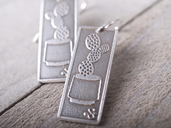 long rectangle etched sterling earrings with prickly pear cactus in a pot shown. French hooks. shown on a barnwood background