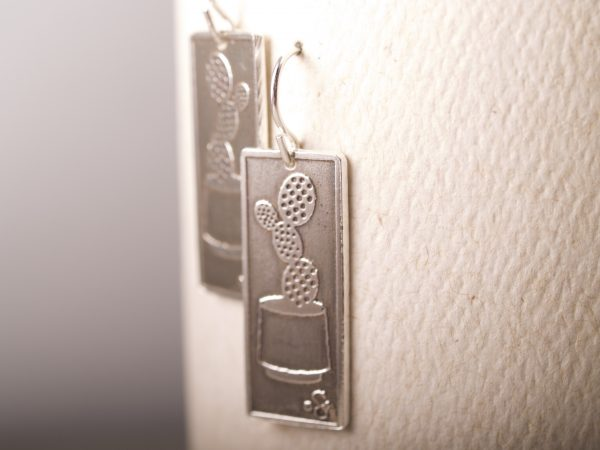 long rectangle etched sterling earrings with prickly pear cactus in a pot shown. French hooks. hanging on white background