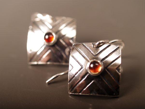 Focus earrings with garnet on gunmetal background