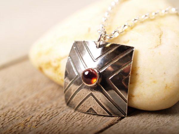 Focus necklace with garnet on sandstone background