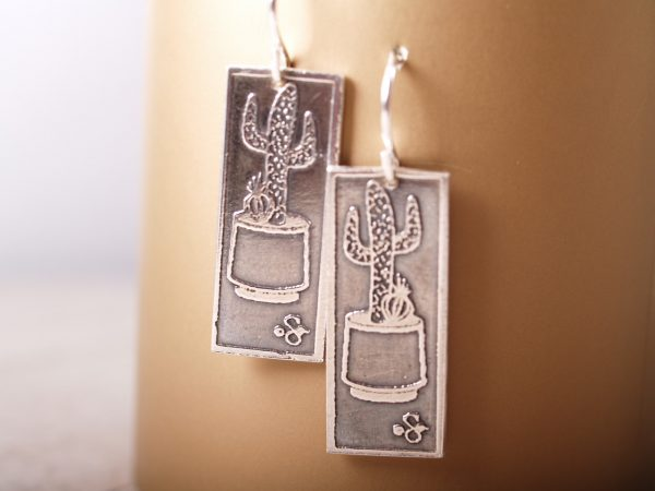 rectangle silver earrings etched with Saguaro cacti in a planters hanging on gold background