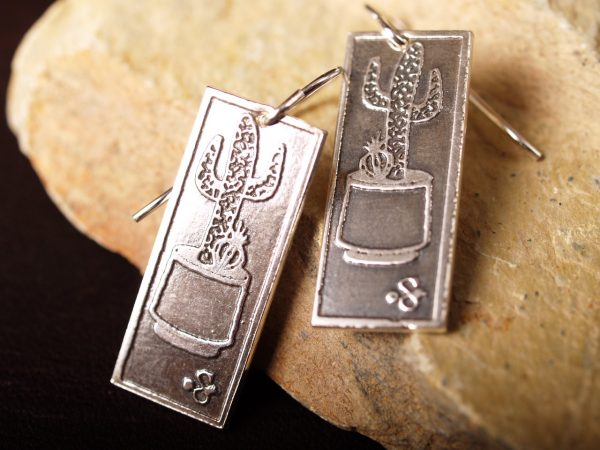 rectangle silver earrings etched with Saguaro cacti in a planters on sandstone background