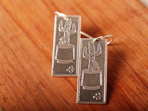 rectangle silver earrings etched with Saguaro cacti in a planter on terra cotta