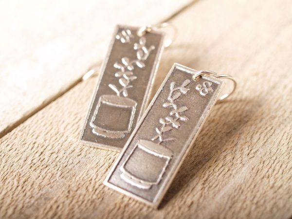 rectangle silver earrings etched with succulent plants in a planters on barnwood background