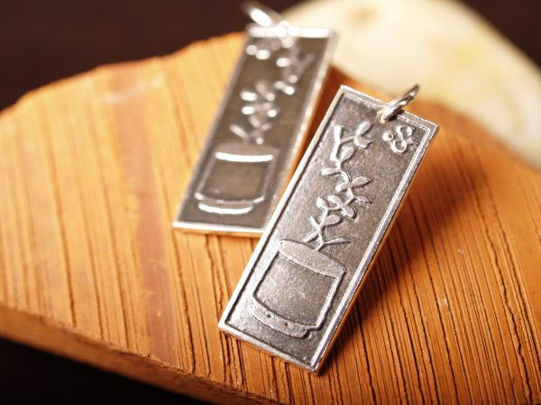 rectangle silver earrings etched with succulent plants in a planters on terra cotta background