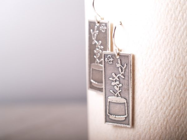 rectangle silver earrings etched with succulent plants in a planters hanging on white background